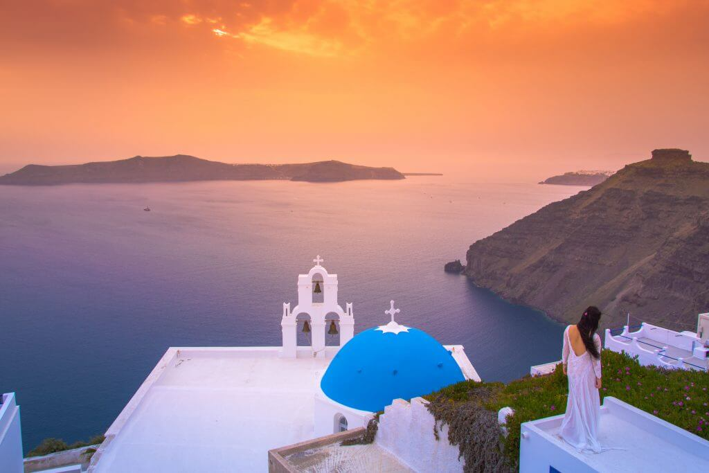 Brilliant sunset at Fira with a church and a bride on a roof, Sa