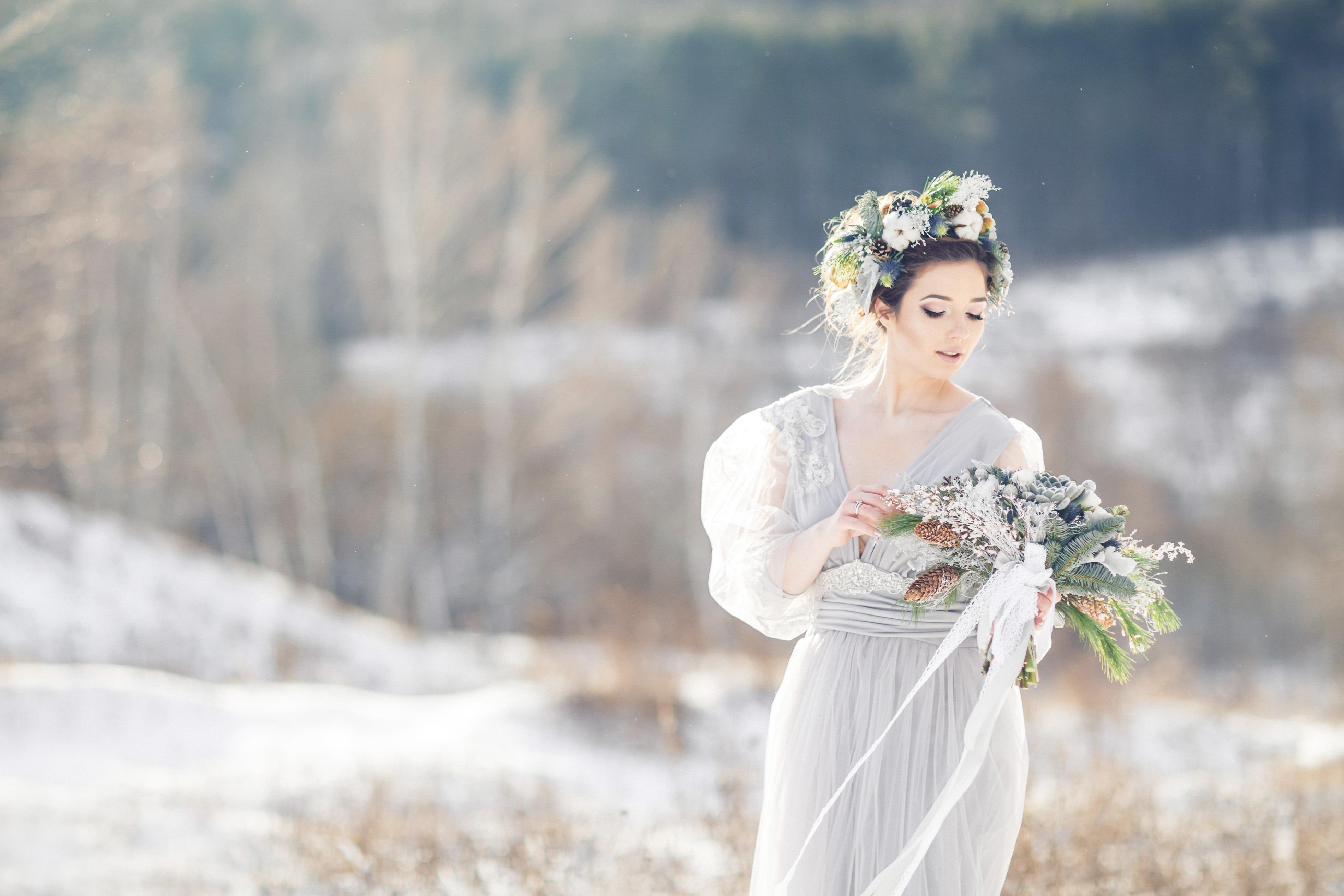 Beautiful bride admiring wedding bouquet. Winter wedding. Winter